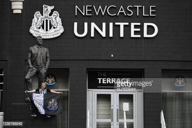 Newcastle United supporter is seen posing in front of the statue of the late former manager Bobby Robson outside the club's stadium St James' Park in...