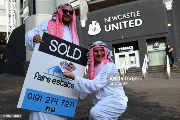 Newcastle United supporters dressed in robes pose with 'sold' placards as they celebrate the sale of the club to a Saudi-led consortium, outside the...