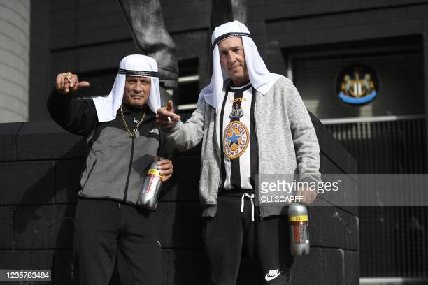 Newcastle United supporters pose wearing head dresses with the statue of late former manager Bobby Robson outside the club's stadium at St James'...