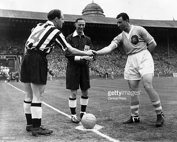 Newcastle United team captain Jimmy Scoular shakes hands with his Manchester City counterpart before the kick off of the 1955 FA Cup final at Wembley...