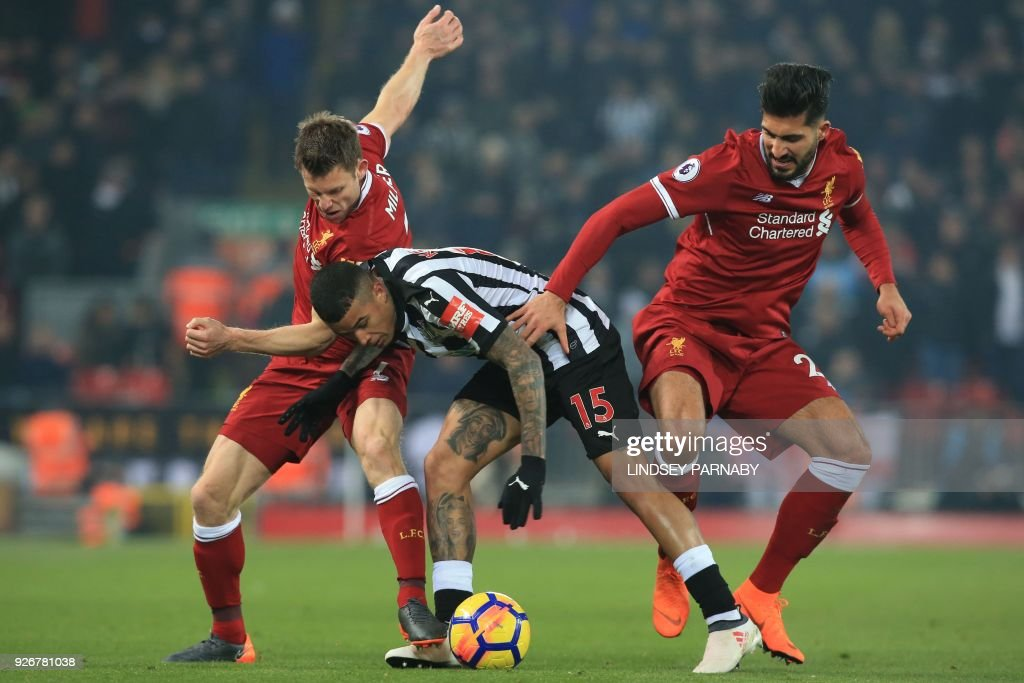 Newcastle United's Brazilian midfielder Kenedy (C) vies with Liverpool's English midfielder James Milner (L) and Liverpool's German midfielder Emre Can (R) during the English Premier League football match between Liverpool and Newcastle at Anfield in Liverpool, north west England on March 3, 2018. / AFP PHOTO / Lindsey PARNABY / RESTRICTED TO EDITORIAL USE. No use with unauthorized audio, video, data, fixture lists, club/league logos or 'live' services. Online in-match use limited to 75 images, no video emulation. No use in betting, games or single club/league/player publications. /