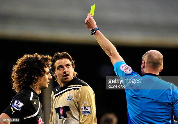 Newcastle United's Dutch goalkeeper Tim Krul is shown a yellow card by referee Lee Mason after his tackle on Fulham's English striker Andy Johnson...