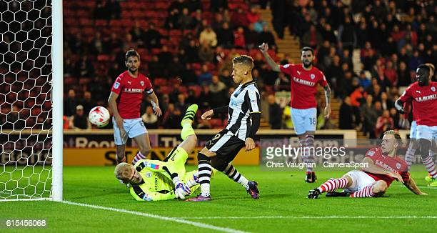 Newcastle United's Dwight Gayle chips the ball over Barnsley's Adam Davies to score the opening goal during the Sky Bet Championship match between...