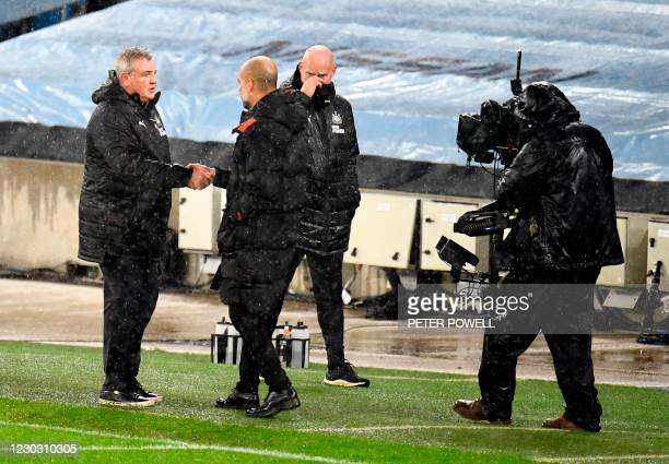 Newcastle United's English head coach Steve Bruce shakes hands with Manchester City's Spanish manager Pep Guardiola after the English Premier League...