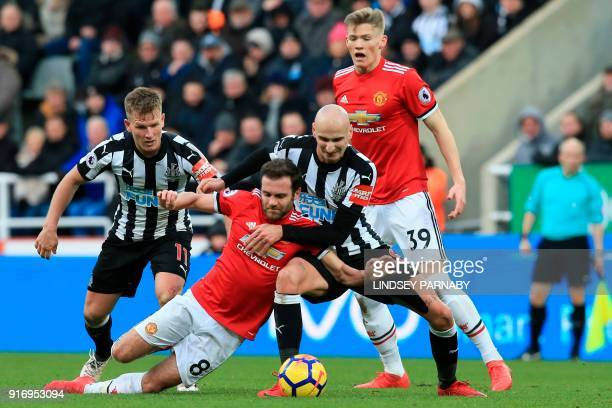 Newcastle United's English midfielder Jonjo Shelvey tangles with Manchester United's Spanish midfielder Juan Mata during the English Premier League...