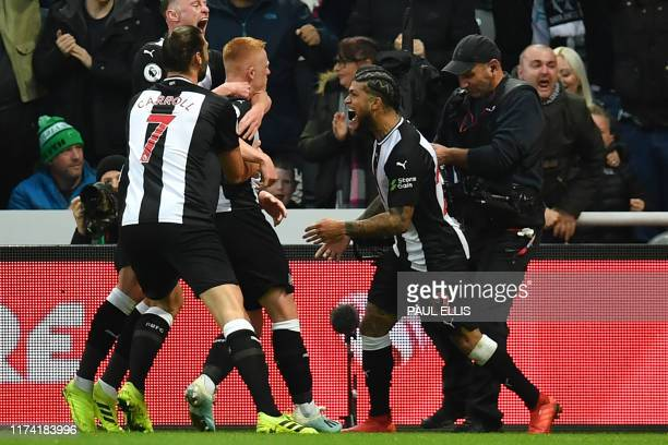 Newcastle United's English midfielder Matthew Longstaff celebrates with teammates after scoring the opening goal of the English Premier League...
