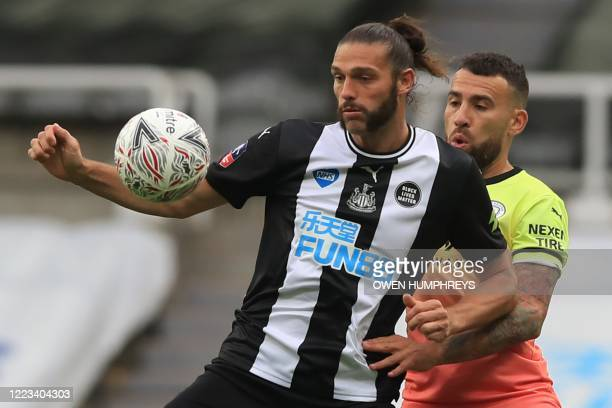 Newcastle United's English striker Andy Carroll holds off Manchester City's Argentinian defender Nicolas Otamendi during the English FA Cup...