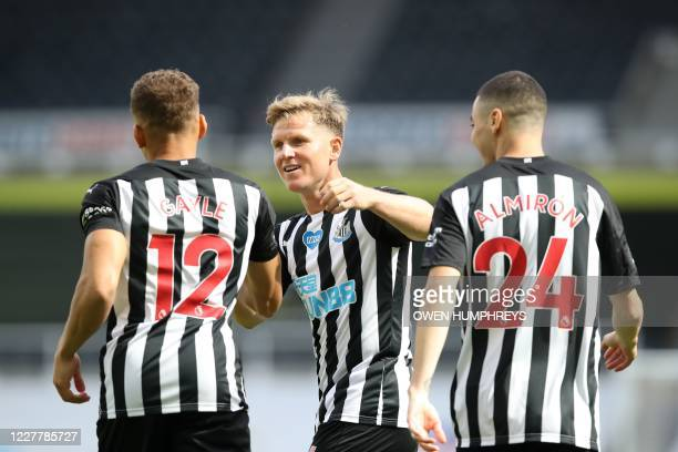 Newcastle United's English striker Dwight Gayle celebrates with Newcastle United's Scottish midfielder Matt Ritchie and Newcastle United's Paraguayan...