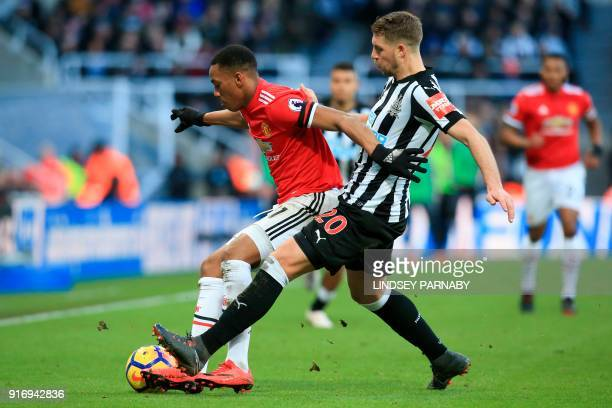 Newcastle United's French midfiielder Florian Lejeune challenges Manchester United's French striker Anthony Martial during the English Premier League...
