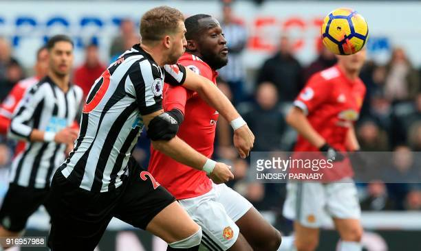 Newcastle United's French midfiielder Florian Lejeune challenges Manchester United's Belgian striker Romelu Lukaku during the English Premier League...