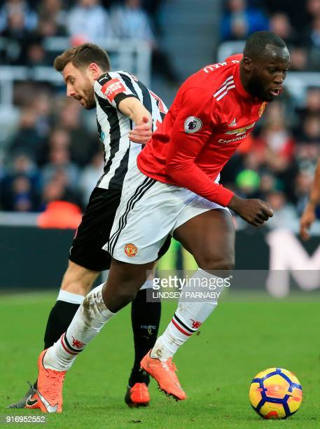 Newcastle United's French midfiielder Florian Lejeune is beaten by Manchester United's Belgian striker Romelu Lukaku during the English Premier...