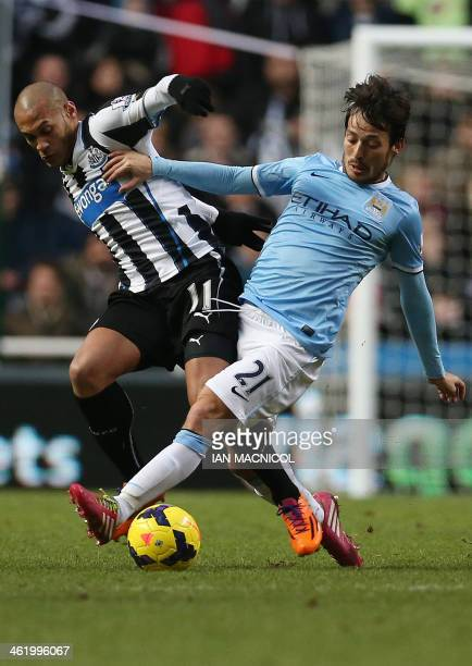 Newcastle United's French striker Yoan Gouffran vies with Manchester City's Spanish midfielder David Silva during the English Premier League football...