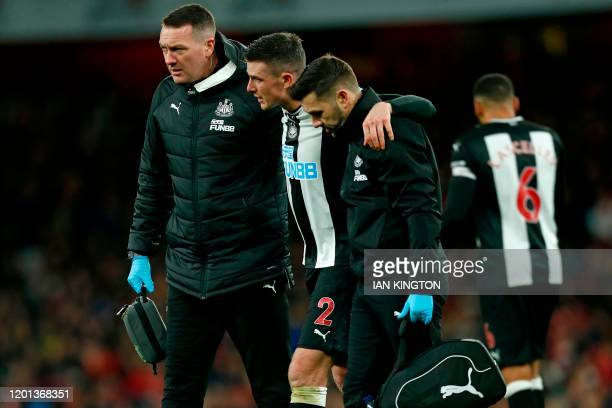Newcastle United's Irish defender Ciaran Clark is helped from the pitch after picking up an injury during the English Premier League football match...