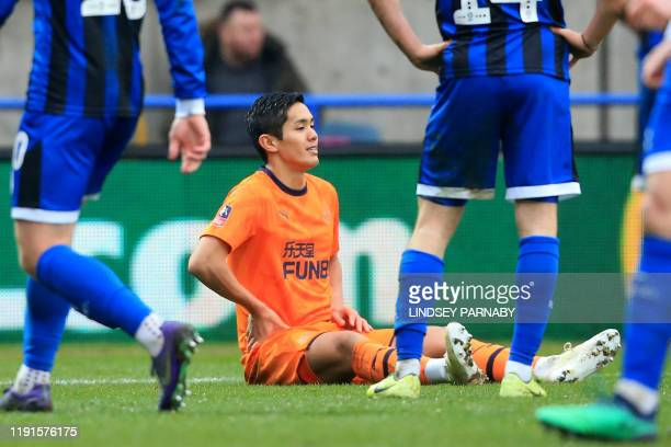 Newcastle United's Japanese striker Yoshinori Muto sits on the pitch before being substituted with an injury during the English FA Cup third round...