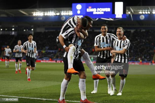 Newcastle United's Paraguayan midfielder Miguel Almiron jumps onto the back of Newcastle United's Spanish striker Ayoze Perez as he celebrates with...