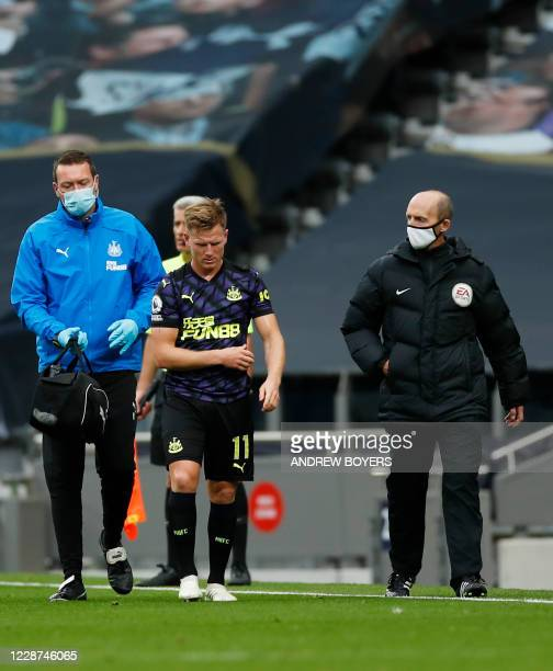 Newcastle United's Scottish midfielder Matt Ritchie leaves the field injured during the English Premier League football match between Tottenham...