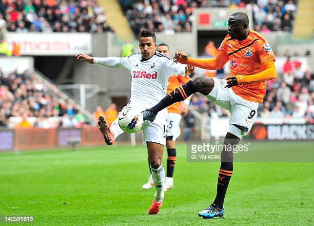 Newcastle United's Senegalese striker Papiss Cisse vies with Swansea City's English midfielder Scott Sinclair during their English Premier League...