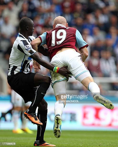 Newcastle United's Senegalese striker Papiss Cisse vies with West Ham United's Welsh defender James Collins during the English Premier League...