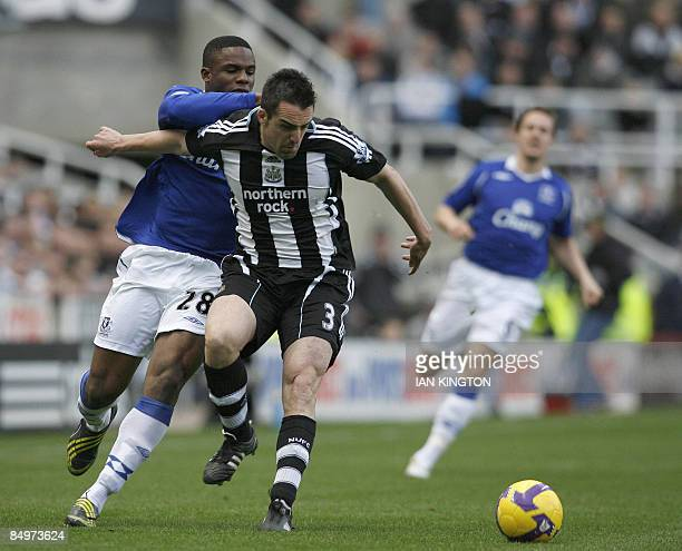 Newcastle United's Spanish footballer Jose Enrique defends against Everton's Nigerian player Victor Anichebe during their Premier League football...