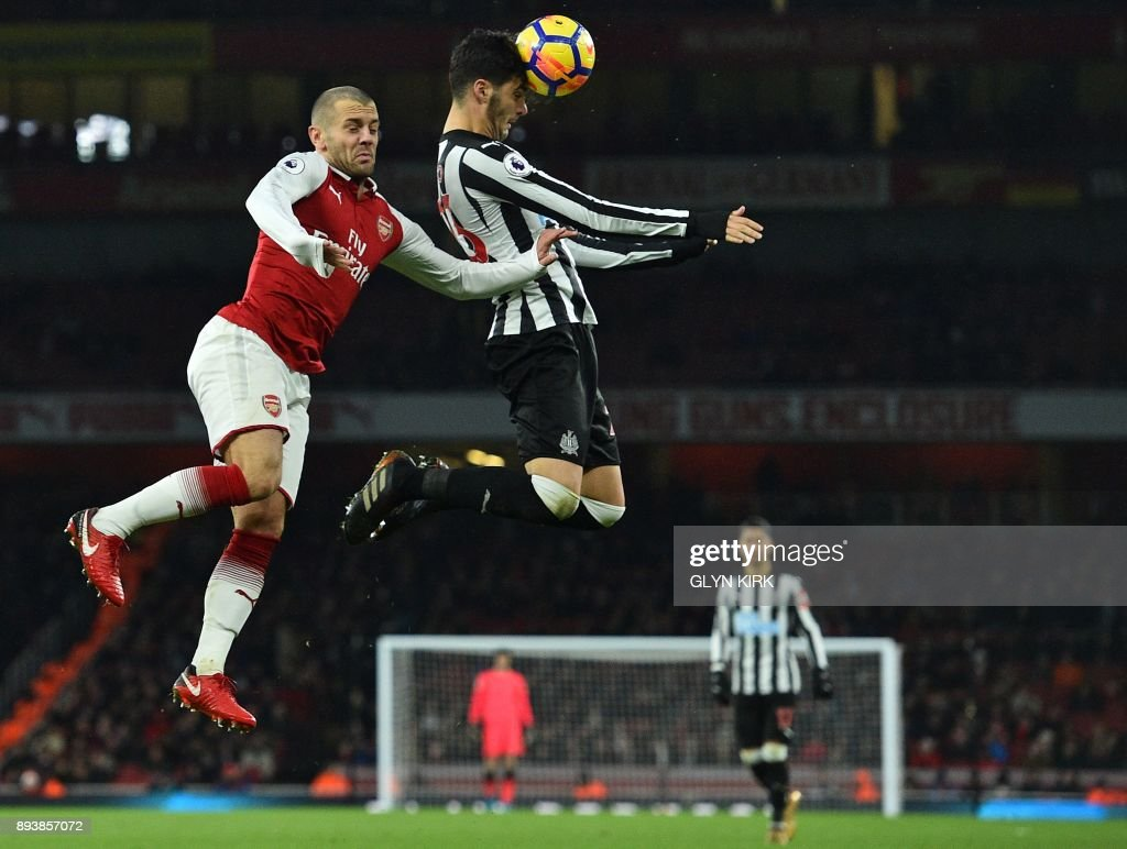 TOPSHOT - Newcastle United's Spanish midfielder Mikel Merino (C) heads the ball under pressure from Arsenal's English midfielder Jack Wilshere during the English Premier League football match between Arsenal and Newcastle United at the Emirates Stadium in London on December 16, 2017. / AFP PHOTO / Glyn KIRK / RESTRICTED TO EDITORIAL USE. No use with unauthorized audio, video, data, fixture lists, club/league logos or 'live' services. Online in-match use limited to 75 images, no video emulation. No use in betting, games or single club/league/player publications. /