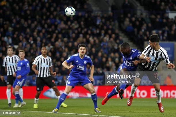 Newcastle United's Spanish striker Ayoze Perez heads home the opening goal under pressure from Leicester City's English-born Jamaican defender Wes...