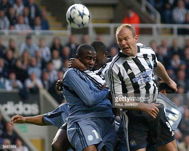 Newcastle's Alan Shearer heads the ball past Marseille's Abdoulaye Meite as he collides with an unidentified Newcastle player during their first leg...