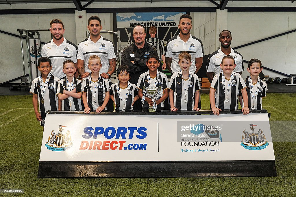 Newcastle's Manager Rafael Benitez (C) poses for a photograph with players and children seen (L-R) Paul Dummett, Aleksandar Mitrovic, Jamaal Lascelles and Vurnon Anita after the Newcastle United Foundation 1892 Cup at The Newcastle United Academy on July 4, 2016, in Newcastle upon Tyne, England.