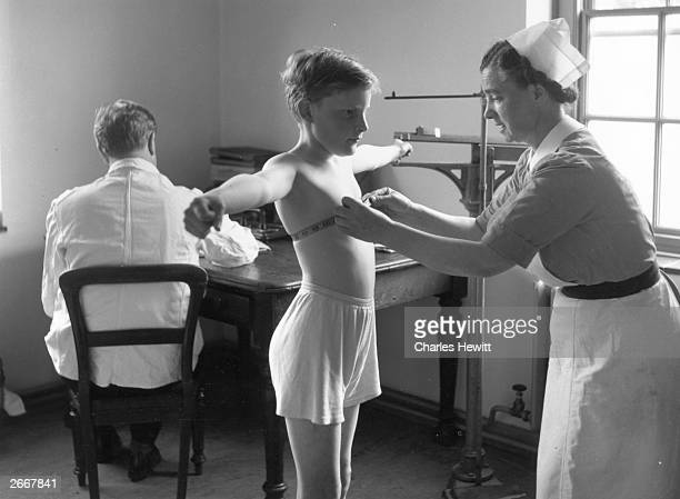 Newcomer to the Royal Commercial Travellers' School, Pinner, Middlesex, is measured and weighed by the school nurse. Original Publication: Picture...
