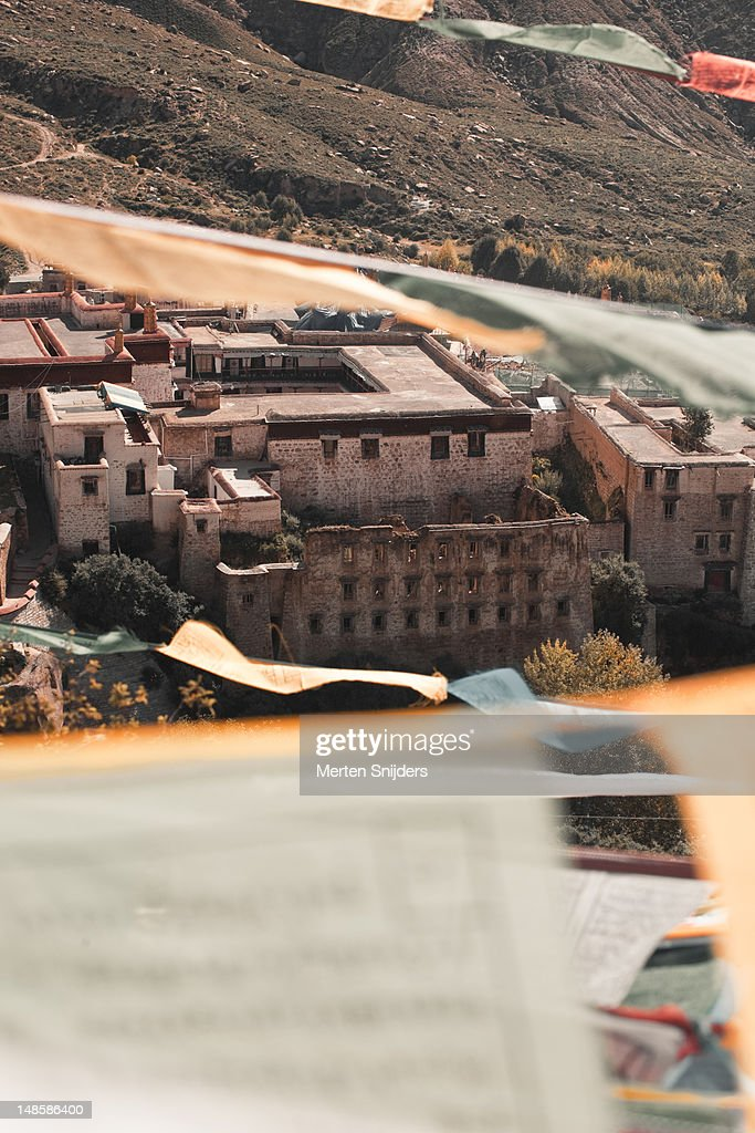 Newer structures behind ruined facade of the old Drepung Monastery seen through prayer flags in the wind. : Stockfoto