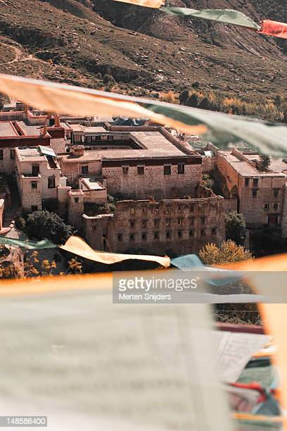 newer structures behind ruined facade of the old drepung monastery seen through prayer flags in the wind. - merten snijders stock pictures, royalty-free photos & images