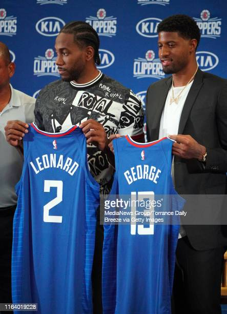 Newest Clippers players Kawhi Leonard and Paul George hold up their jerseys during a press conference at the Green Meadows Recreation Center in Los...