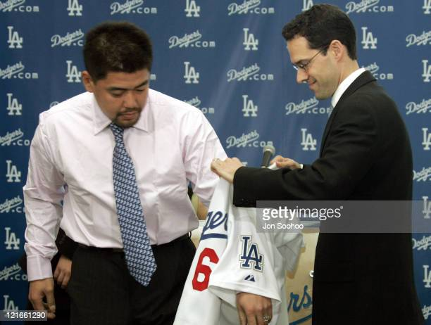 Newest Los Angeles Dodgers Norihiro Nakamura receives his jersey from team general manager Paul Depodesta at Dodger Stadium in Los Angeles California...