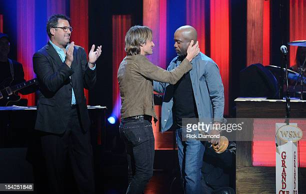 Newest member of the Grand Ole Opry Darius Rucker gets surprised by Keith Urban while Vince Gill applauds during Rucker's induction into The Grand...