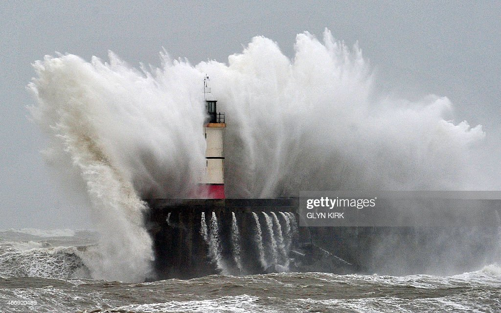 Newhaven Lighthouse is battered by waves during stormy weather in Newhaven on the southern coast of England on February 5, 2014. More than 8,000 homes were without power in southwest England after fresh storms battered the region, sending huge waves crashing onto the coastline and damaging sea defences.