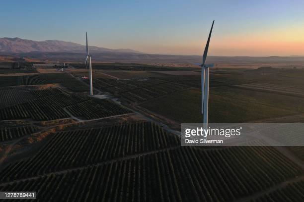 Newky-constructed wind turbines tower over orchards and vineyards at sunrise as the 2020 wine grape harvest nears its end on October 5, 2020 at Tel...
