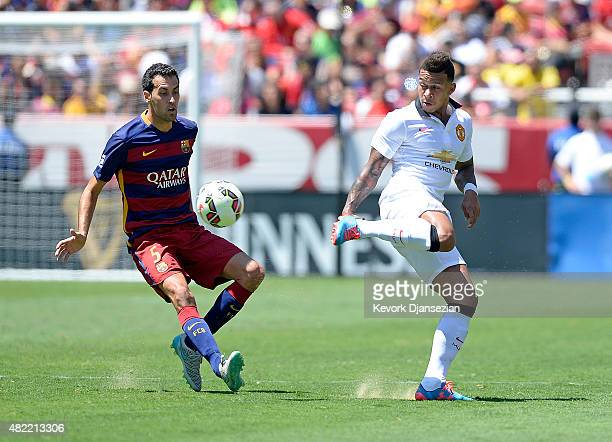 Newly acquired midfielder Memphis Depay of Manchester United makes a back heel pass against Sergio Busquets of FC Barcelona during their friendly...