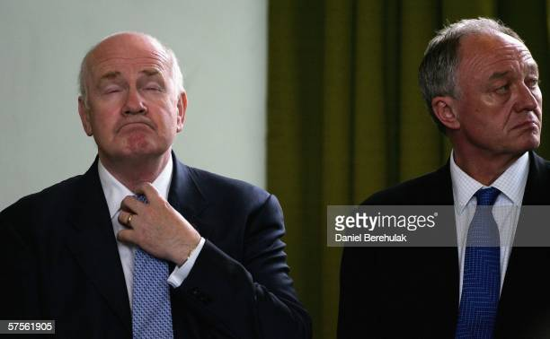 Newly appointed British Home Secretary John Reid adjusts his tie as London Mayor Ken Livingstone looks on during a commendation ceremony on May 9,...