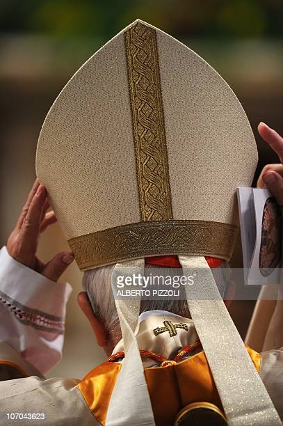 Newly appointed cardinal takes off his tiara before recieving his cardinal ring from Pope benedict XVI during the Eucharistic celebration with the...