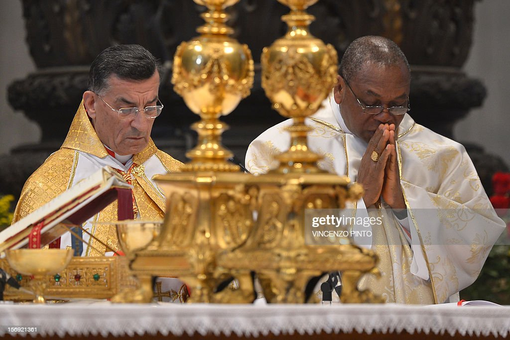 Newly appointed cardinals Colombian Ruben Salazar Gomez (L) and Nigerian John Onaiyekan stand during a Holy mass led by the pontif with new cardinals on November 25, 2012 at St Peter's basilica at the Vatican. Pope Benedict XVI the day before consecrated six non-European prelates as new members of the College of Cardinals in a development welcomed by critics concerned that the body which will elect the future pope is too Euro-centric.