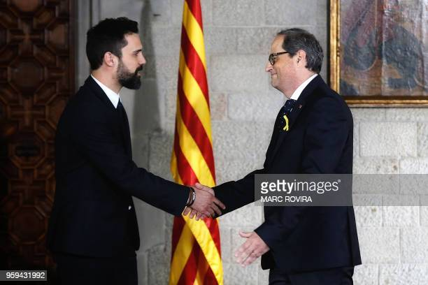 Newly appointed Catalan president Quim Torra shakes hands with Catalan parliament speaker Roger Torrent after taking office during an official...