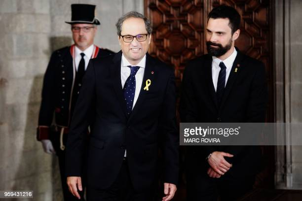 Newly appointed Catalan president Quim Torra smiles as he arrives with Catalan parliament speaker Roger Torrent to take office during an official...