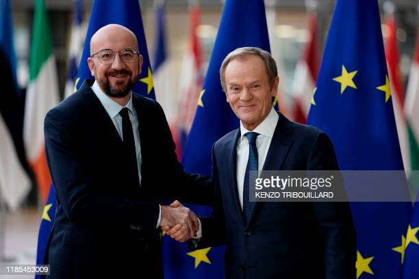 Newly appointed European Council President Charles Michel shakes hands with outgoing European Council President Donald Tusk during the handover...