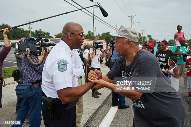 Newly appointed Ferguson Police Chief Andre Anderson shakes hands with participants during a march of solidarity on West Florissant Avenue August 8...