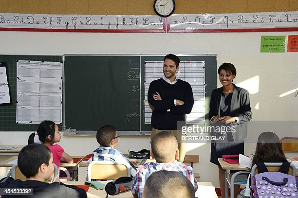 Newly appointed French Education Minister Najat VallaudBelkacem stands on September 3 2014 next to a teacher in a class at the Denis Diderot...