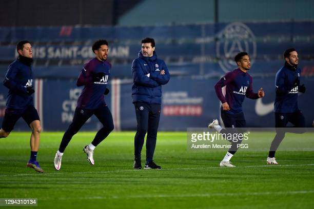 Newly appointed head coach Mauricio Pochettino looks on as players run beside him during a Paris Saint-Germain training session at Ooredoo Center on...