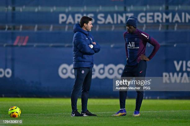 Newly appointed head coach Mauricio Pochettino speaks with Moise Kean during a Paris Saint-Germain training session at Ooredoo Center on January 03,...