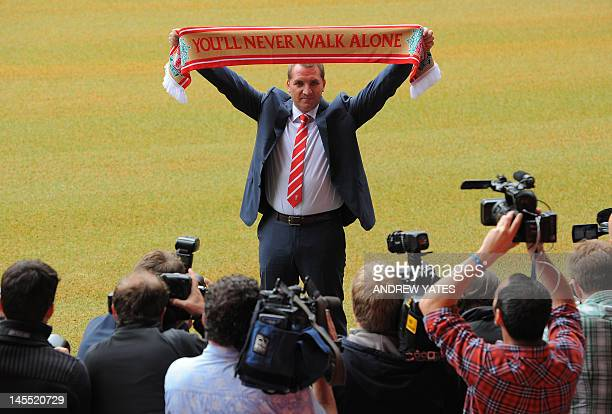 Newly appointed Liverpool football club manager Brendan Rodgers poses for photographers with a team scarf to announce his arrival at Anfield in...