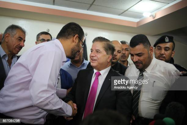 Newly appointed Palestinian Minister of Health Jawad Awwad shakes hands while he tours a pharmaceutical warehouse in Gaza City Gaza on October 3 2017...
