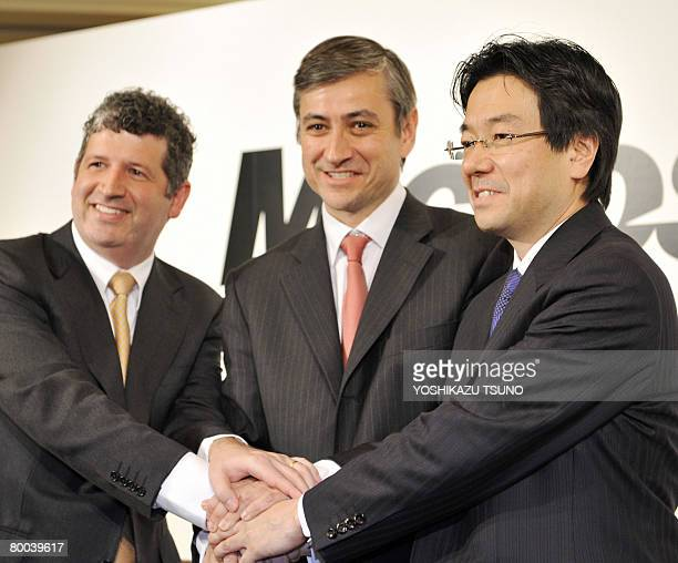 Newly appointed president of Microsoft Japan Yasuyuki Higuchi shakes hands with Microsoft International president JeanPhilippe Courtois and outgoing...