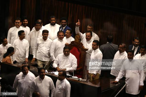 Newly appointed prime minister Mahinda Rajapaksa's government parliamentarians sit on speaker chair as shout slogans prior the parliament session...
